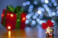 Il fondo per il messaggio di natale con rosso di Santa ha acceso l'albero di Natale del contenitore e di regalo con le luci di na fotografia stock libera da diritti