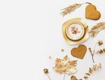 Il fondo piano di disposizione con la tazza di caffè dell'oro con cuore ha modellato i biscotti Immagini Stock Libere da Diritti
