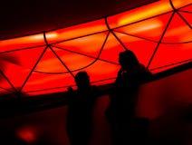 Il fondo scuro della gente della sfuocatura dietro vetro ed ha luce ultravioletta rossa Fotografia Stock Libera da Diritti
