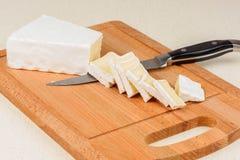 Il formaggio è affettato su un bordo di legno Fotografia Stock Libera da Diritti
