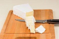 Il formaggio è affettato su un bordo di legno Fotografia Stock