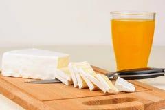 Il formaggio è affettato su un bordo di legno e su un vetro di succo d'arancia per la prima colazione Fotografie Stock Libere da Diritti