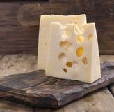 Il formaggio con i fori è parti incise su un bordo di legno, un prodotto lattiero-caseario utile Alimento saporito Foto stile cou Immagine Stock