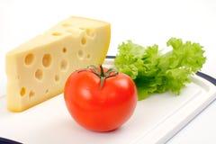 Il formaggio, il pomodoro e l'insalata rivestono su una scheda bianca Fotografia Stock