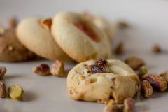 Il forno dei biscotti di burro del pistacchio fresco, con i pistacchi spruzzati dentro sopra loro ha isolato in un fondo bianco fotografia stock
