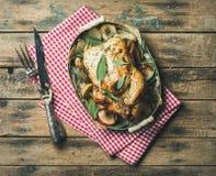 Il forno ha arrostito l'intero pollo in vassoio sopra fondo di legno immagini stock
