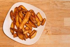 Il forno ha cotto le patatine fritte su un piatto bianco Immagini Stock