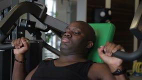 Il forte afroamericano oscilla i suoi muscoli del braccio sulla macchina di addestramento archivi video