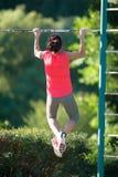 Il forte atleta della donna è Chin-UPS e Pullups che si prepara su un aban Fotografia Stock Libera da Diritti