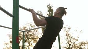 Il forte atleta negli sportclothes neri che iniziano fare tira su sulla barra orizzontale Uomo che si esercita all'aperto Alberi  stock footage