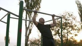 Il forte atleta nel fare nero degli sportclothes tira su sulla barra orizzontale Equipaggia la forma fisica con cielo blu e gli a stock footage
