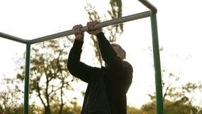 Il forte atleta nel fare nero degli sportclothes tira su sulla barra orizzontale Il Sun splende sui precedenti e sugli alberi int stock footage