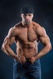 Il forte culturista sforza i suoi muscoli potenti Fotografia Stock