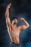 Il forte culturista sforza i suoi muscoli potenti Immagini Stock Libere da Diritti