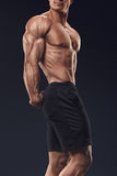 Il forte e giovane culturista bello dimostra la sua t muscolare Immagini Stock