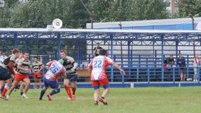 Il forte funzionamento del giocatore di rugby con una palla e le protezioni lo bloccano video d archivio