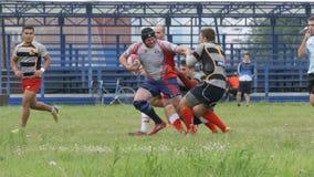 Il forte funzionamento e le protezioni del giocatore di rugby lo bloccano video d archivio