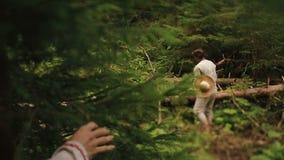 Il forte giovane taglialegna taglia la legna da ardere a pezzi nella foresta mentre belle giovani driadi della foresta che spiano stock footage