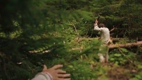 Il forte giovane taglialegna taglia la legna da ardere a pezzi nelle belle giovani driadi della foresta della foresta che spiano  video d archivio