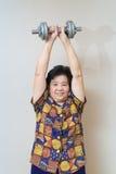 Il forte sollevamento senior asiatico della donna pesa, nel colpo dello studio, lo speci fotografie stock