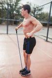 Il forte tipo atletico mette in mostra l'estensore di allungamenti dell'uomo Fotografia Stock