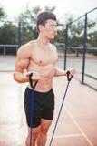 Il forte tipo atletico mette in mostra l'estensore di allungamenti dell'uomo Fotografie Stock Libere da Diritti