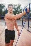 Il forte tipo atletico mette in mostra l'estensore di allungamenti dell'uomo Immagini Stock