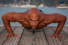 Il forte uomo che fa la pressa aumenta Fotografia Stock