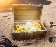 Il forziere riempito di bitcoins circondati da incandescenza dorata parzialmente burried in sabbia fotografia stock