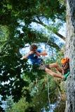 Il fotografo appende su una corda sulla scogliera e spara agli scalatori Fotografie Stock Libere da Diritti