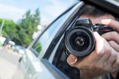 Il fotografo con la macchina fotografica prende la foto dalla finestra di automobile Fotografia Stock Libera da Diritti