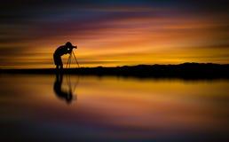 Il fotografo della siluetta prende a foto la bella vista sul mare al tramonto immagini stock libere da diritti