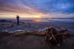 Il fotografo ed il sole hanno messo sul Ne nero dell'isola del sud di hokitika della spiaggia Fotografie Stock Libere da Diritti