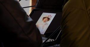 Il fotografo lancia le foto del modello dopo il photosession sul computer portatile archivi video