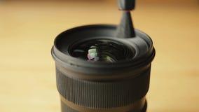 Il fotografo o il videographer libera la lente anteriore da polvere e dalla sporcizia con l'aiuto di una spazzola di pulizia prof stock footage