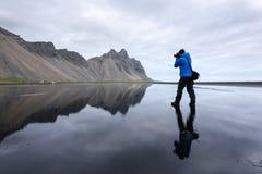 Il fotografo prende la foto vicino alle montagne famose di Stokksnes Fotografie Stock
