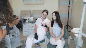 Il fotografo prende le immagini del dentista e del paziente in clinica dentaria, movimento lento stock footage