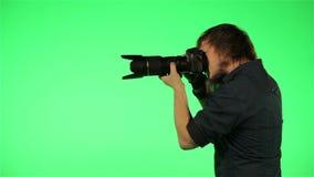 Il fotografo prende le immagini su uno schermo verde video d archivio