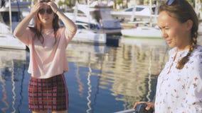 Il fotografo professionista, immagini nel porto marittimo contro il contesto degli yacht, una donna preme un bottone ed i colloqu stock footage