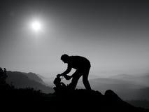 Il fotografo professionista sta imballando la macchina fotografica nello zaino Il paesaggio vago del fogy, balza l'alba nebbiosa  Immagini Stock