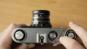 Il fotografo riavvolge il film di vecchia macchina da presa e preme il bottone archivi video
