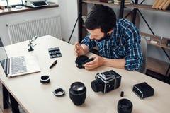 Il fotografo smonta la macchina fotografica della foto nel luogo di lavoro Fotografie Stock