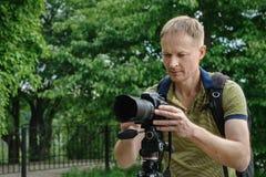 Il fotografo sta fotografando con un treppiede fotografia stock