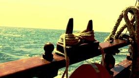Il frammento del lato del ` s dell'yacht con le corde, l'yacht naviga sul mare durante il tramonto archivi video