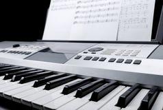 Il frammento della tastiera elettronica del sintetizzatore con i bottoni e la musica di controllo nota gli strati Fotografie Stock Libere da Diritti