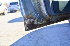 Il frammento di un'automobile con ruggine l'elemento della carrozzeria ? corroso Concetto: resistenza della corrosione, riparazio immagini stock