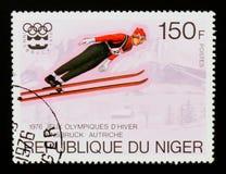 Il francobollo del Niger mostra Ski Jumping, serie di Innsbruck dei giochi olimpici, circa 1976 Fotografia Stock Libera da Diritti