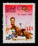 Il francobollo della Guinea-Bissau mostra il Manifestazione-salto, serie dei giochi olimpici, circa 1983 Fotografie Stock Libere da Diritti