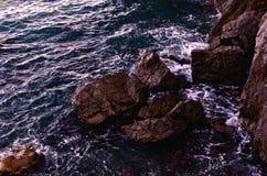 Il frangente ondeggia vicino ai massi costieri Immagine Stock