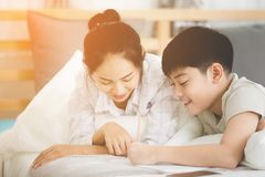 Il fratello e la sorella asiatici felici riposano sul letto e sulla scrittura Immagini Stock